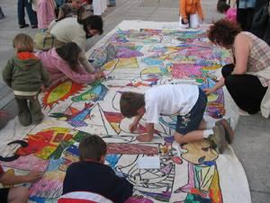 Niños pintando un mural en defensa de los Derechos de los Niños y las Niñas, actividad organizada por AI Pamplona.