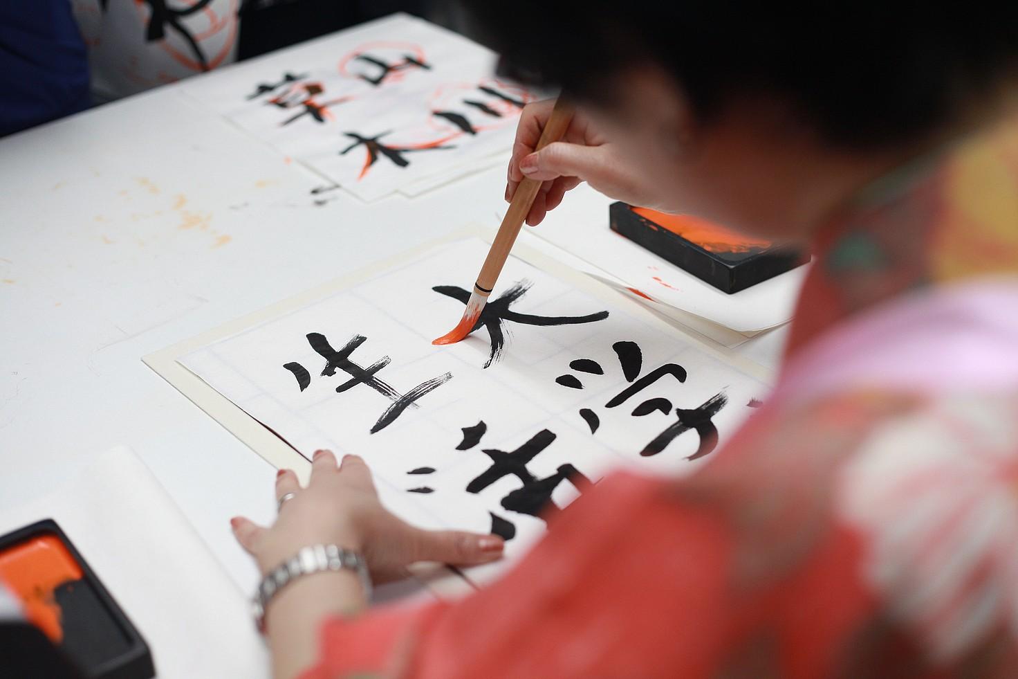 Mujer japonesa escribiendo sobre una lámina de papel